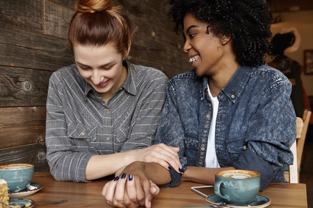 Love and relationships. Cheerful African lesbian with braces and Afro hairstyle holding hands with her cute redhead girlfriend, talking to each other at cafe, sharing happy and sweet moments together Foto de archivo