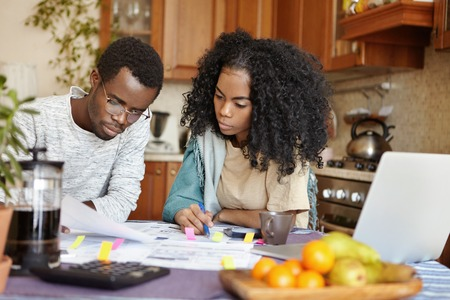 Indoor shot of young African family analyzing their finances, planning budget, accounting domestic expenses and calculating unpaid bills, sitting at kitchen table with papers, calculator and laptop