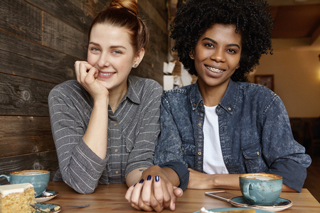 Interracial gay couple relaxing indoors. Cute Caucasian woman with hair bun holding hand of her stylish African girlfriend during lunch. Two lesbians celebrating their anniversary at restaurant Zdjęcie Seryjne - 72035695