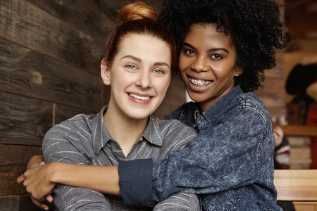 Happy young interracial homosexual couple spending nice time together at modern coffee shop. African lesbian holding tight her beautiful Caucasian girlfriend. Candid situation with real people Stock Photo