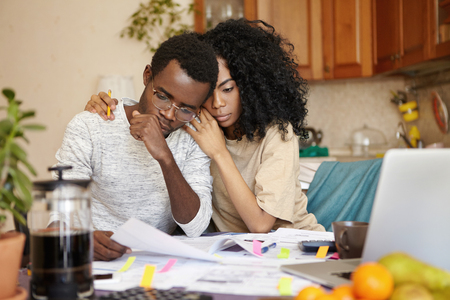No money. Depressed desperate bankrupt young dark-skinned family feeling financial stress while reading notification, informing about eviction from their house because of non-payment for rent Stock Photo