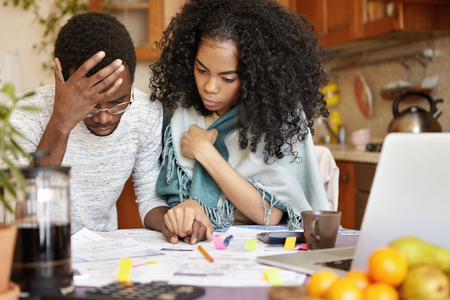 Young African-American couple with many debts calculating gas and electricity bills while doing paperwork together, feeling stressed, realizing that they are no longer able to cover family expenses