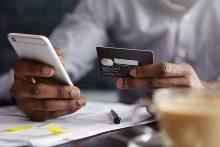 Bijgesneden opname van Afro-Amerikaanse zakenman betalen met creditcard online bestellingen via internet. Succesvol zwart mannetje dat plastic kaart houdt die transactie maakt gebruikend mobiel bankwezentoepassing Stockfoto