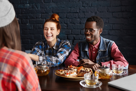 stylish hair: Three students dining at cafe after college. Beautiful girl with ginger hair and stylish African man smiling happily havinglively conversation with their common female friend sitting in foreground