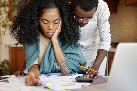 People, family budget, finances and payments concept. African-American man wearing glasses helping his frustrated wife doing paperwork, analyzing papers, calculating expenses, using calculator