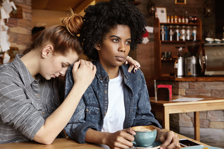 argues: Young Caucasian female sitting at cafe, saying sorry, trying to apologize to her mad and angry African girlfriend after dispute or quarrel, begging for forgiveness. Disagreement in relationships
