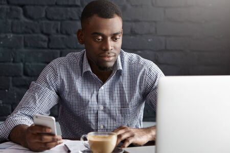 formal shirt: Handsome young African man in formal shirt surfing internet on mobile phone while calculating bills online and reviewing finances, using laptop computer during lunch break at modern restaurant Stock Photo