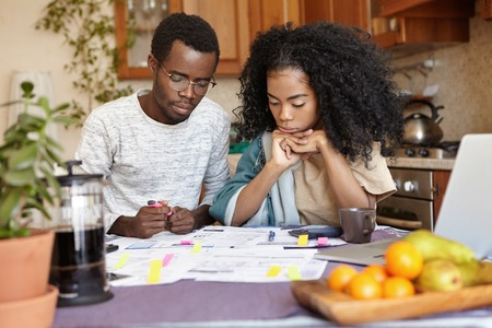 Young African couple doing paperwork together, sitting at kitchen table with lots of papers, calculator and laptop, looking frustrated. Dark-skinned family calculating domestic budget at home Banco de Imagens