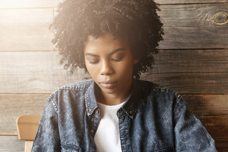 Portrait of sad young African female with stylish haircut dressed in denim shirt looking down with serious expression, unhappy after break up with her man, sitting at cafe with wooden walls alone