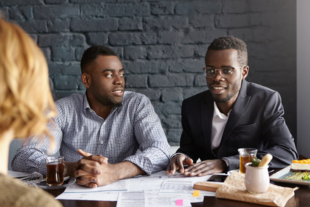 recruiters: Two handsome confident African-American recruiters in formal wear asking tricky questions to female applicant, checking her during job interview, sitting at desk with papers. Human resources concept