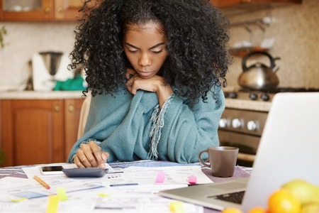 Single African-American mother with many debts feeling stressed calculating finances, siting at kitchen table with papers, laptop, making calculations on calculator, trying to make both ends meet Banco de Imagens