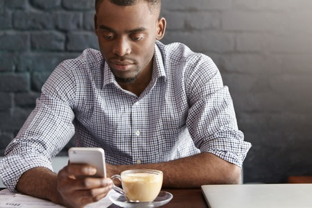 his shirt sleeves: Handsome African office worker wearing checkered shirt with rolled up sleeves enjoying online communication, surfing internet on his mobile phone while having coffee during lunch at restaurant