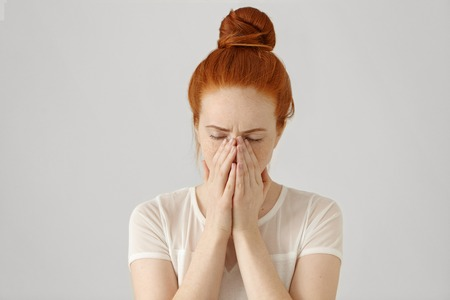 Portrait of unhappy and depressed young Caucasian woman with ginger hair feeling ashamed or sick, covering face with both hands, keeping eyes closed. Human face expressions and emotions concept