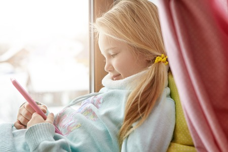 Charming happy blonde female child with messy ponytail using wireless internet connection on smart phone at home, enjoying online communication, messaging friends, sitting on windowsill alone Stock Photo