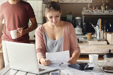 노트북 및 계산기, 그녀의 뒤에 서있는 그녀의 남편 부엌 식탁에서 서류를 통해 작업하는 동안 모기지 용어의 연장에 은행에서 알림을 읽고 행복 아름