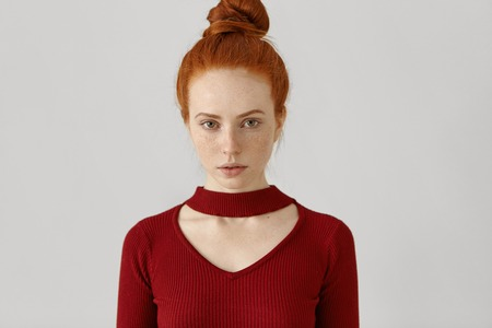 Beauty, style, fashion, clothing and design concept. Gorgeous luxurious Caucasian redhead woman with hair bun and freckles wearing stylish red dress with geometrical cut out before going out on date Imagens - 73222503
