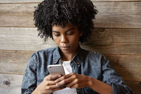 newsfeed: Beautiful young dark-skinned woman wearing trendy jeans jacket typing sms on her generic smart phone, browsing newsfeed via social networks online while waiting for friends at cafe with wooden walls Stock Photo