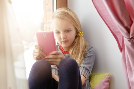 blonde teenager: Indoor shot of adorable little girl wearing her blonde hair in messy ponytail relaxing on windowsill, using wi-fi on mobile phone in pink case, enjoying online communication after classes at school