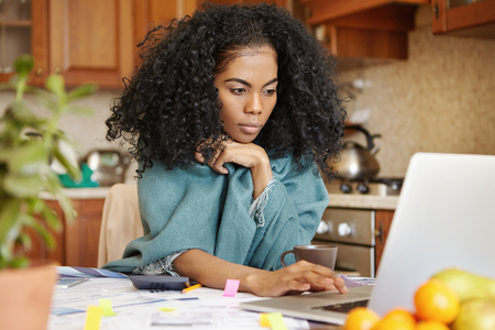 Beautiful young dark-skinned woman with Afro hairstyle wearing wrap keeping hand on touchpad of open laptop computer , looking at screen with serious concentrated expression, paying bills online