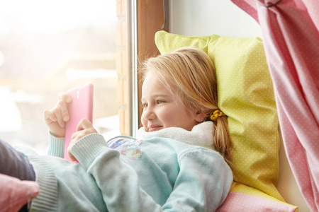 Cheerful little girl in blue sweater lying on windowsill with pillows, happy with using new mobile phone, bought by parents on her birthday, enjoying wireless internet connection, messaging friends Stock Photo
