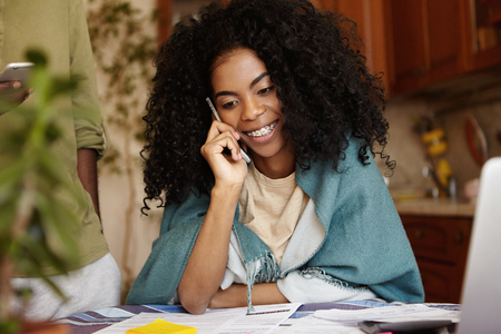 People, technology and communication concept. Attractive young dark-skinned female with Afro haircut sitting at kitchen table in wrap, having phone conversation with friend while calculating bills
