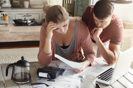 Worried couple reviewing their family finances and calculating expenses, trying to save some money to pay off loan in bank, reviewing bills together, using laptop and calculator at kitchen table
