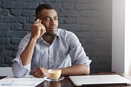 his shirt sleeves: Successful African businessman in shirt with rolled up sleeves having phone call with his partner while resting alone at cafe during coffee break, sitting at table with laptop, documents and cup