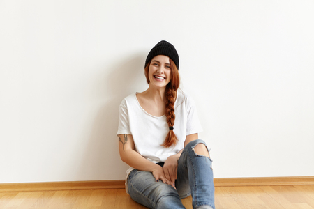 Indoor shot of beautiful happy Caucasian student girl with charming smile wearing white t-shirt, hat and ragged jeans, sitting on floor, leaning on blank wall while relaxing at home after university