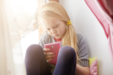 Blonde little girl with loose ponytail looking at screen of her mobile phone in pink case with concentrated expression while playing video games, siting on windowsill after classes at school