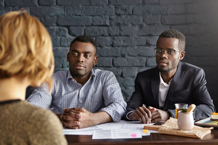 interviewed: People, business, human resources and recruitment concept. Unrecognizable female candidate with short hair is interviewed by two attractive businessmen during job interview for accountant position Stock Photo