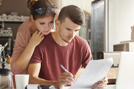 European family managing domestic finances at home. Unemployed man with serious and concentrated look filing in job application form while his wife standing behind him, looking worried and nervous Stockfoto