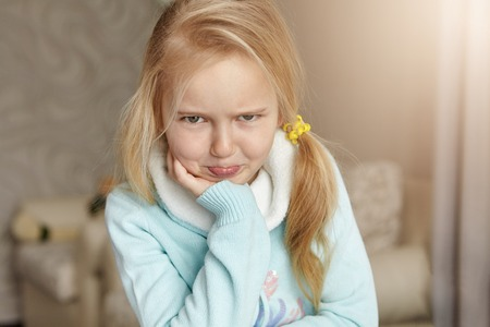 Indoor shot of unhappy and offended blonde Caucasian little girl with messy hair pouting her lips, because of being punished for misbehaviour by her parents, sitting in bedroom alone and crying Stock Photo