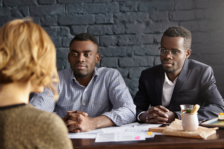 recruiters: Back view of young woman with short haircut sitting at desk in front of future boss and HR. Two African-American recruiters interrogating potential worker of their company during job interview