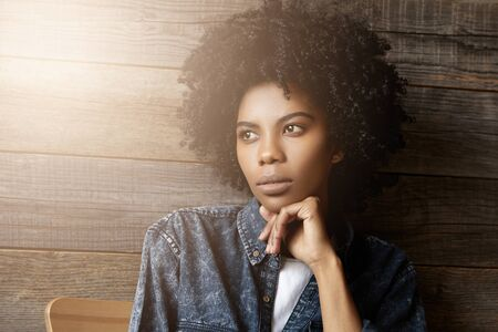 Close up portrait of attractive good-looking young Africa female with curly haircut resting chin on her hand, having wistful reflective expression, posing indoors, dressed in trendy jeans jacket Stock Photo