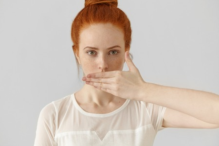 horrify: Portrait of attractive young redhead woman covering mouth with hand, keeping secret, not supposed to tell anything, looking at camera with serious eyes, posing isolated against white wall background