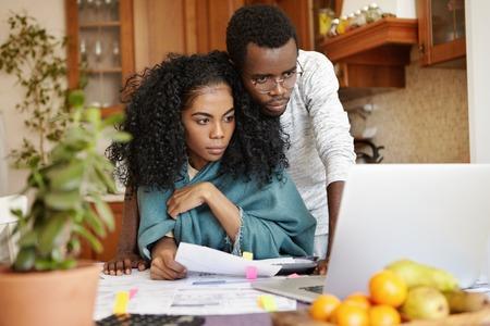 koncentrovaný: Vnitřní záběr mladého páru tmavé pleti spravujícího rodinný rozpočet doma, zaplacení poplatek za plyn a elektřinu online poprvé, při pohledu na obrazovku notebooku se soustředěnými zmatenými výrazy