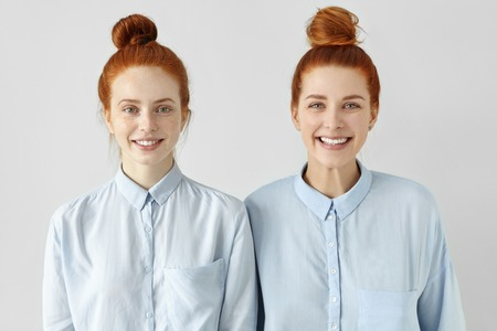 Two young redhead Caucasian females looking alike wearing same formal light-blue shirts, looking at camera, smiling happily, standing close to each other against white studio wall background Banco de Imagens