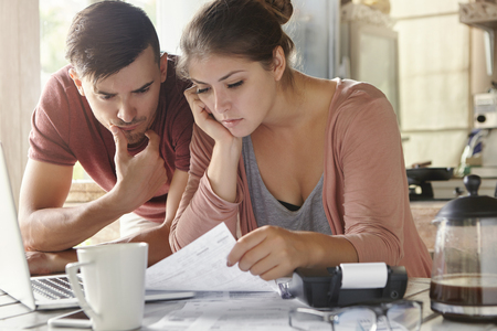 Young female and her unemployed husband with many debts doing paperwork together in kitchen, reading notification, informing that they must move out from their apartment because of non-payment