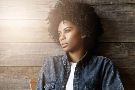 Stylish dark-skinned girl with Afro hairstyle dressed in trendy jeans jacket having rest indoors at coffee shop, looking away with serious expression on her face, thinking of something important