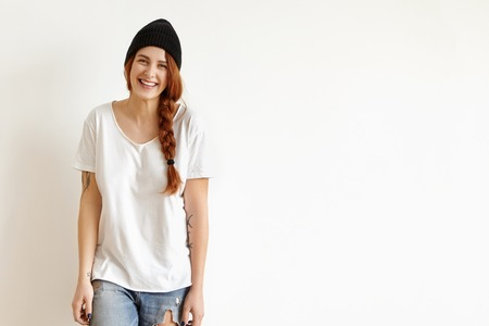 People, style, fashion and design. Indoor shot of pretty girl in stylish black hat, white t-shirt and ragged jeans smiling happily, standing isolated against studio wall with copy space for your text Stock Photo