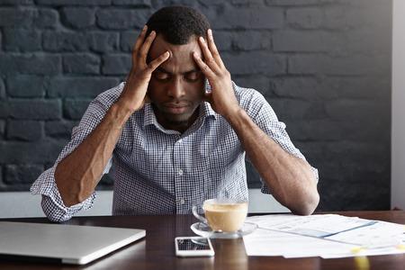 Frustrierter junger African-Americangeschäftsmann, der starke Kopfschmerzen hat, seine Tempel drückend, bei der Arbeit gestresst fühlend und sitzen am Schreibtisch mit generischer Laptop-Computer, Dokumenten, Becher und Handy