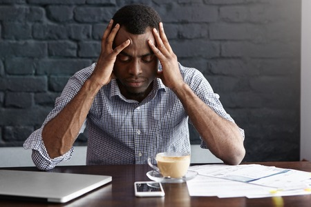 Frustrated young African-American businessman having bad headache, squeezing his temples, feeling stressed at work, sitting at desk with generic laptop computer, documents, mug and mobile phone Stockfoto