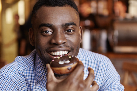 Portrait of cheerful young African male wearing formal checkered shirt holding glazed doughnut, ready to bite it, looking at camera with happy smile. Joyful student eating pastry during lunch break
