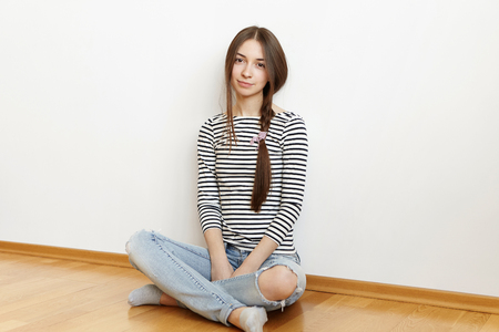 People and lifestyle concept. Indoor shot of beautiful teenage girl with messy hair in loose braid wearing casual striped long-sleeve top and ragged jeans sitting cross-legged on floor at home Stock Photo