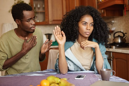 Sad African-American male in glasses holding hand on chest, apologizing to his angry and mad wife, who ignoring him, refusing to forgive him for cheating on her. People and relationships concept