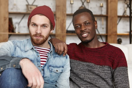 Homosexual love and relationships concept. Interracial gay couple relaxing at cafe: African-American man in sweater holding hand on his stylish bearded Caucasian boyfriends shoulder in trendy hat Фото со стока