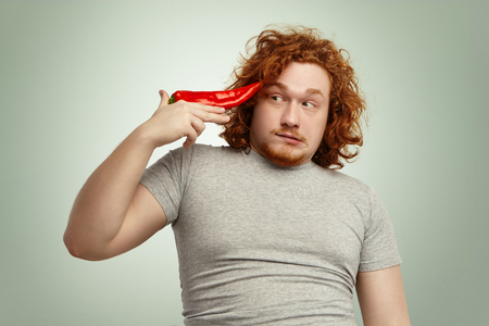 belly pepper: Portrait of funny male with ginger curly hair holding big red pepper at temple like gun, about to shoot himself because of unbearable vegetable diet, looking sideways with scared fearful expression