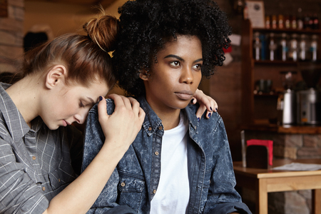 cheater: Please forgive me. Mad angry black woman dressed in denim jacket pouting, ignoring apologies of her white redhead female partner who hugging her and begging for forgiveness after having quarrel Stock Photo
