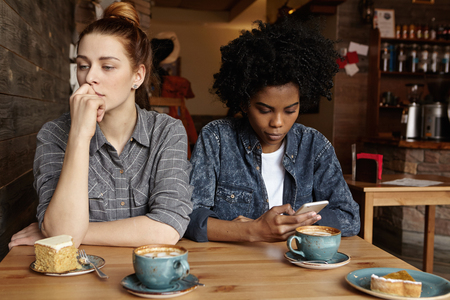 Two unhappy lesbians not talking to each other after having quarrel during lunch at coffee shop: sad redhead woman feeling lonely while her African girlfriend sitting next to her, using mobile phone