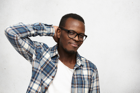 embarassment: Studio shot of handsome African American hipster wearing trendy glasses and checkered shirt over white t-shirt, holding hand behind, scratching his head, smiling shyly, pleased with compliment